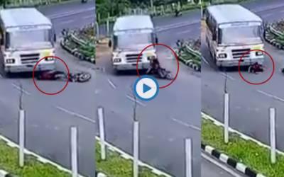 موٹر سائیکل سوار نوجوان بس کے نیچے آگیا؛ دل دہلادینے والی ویڈیو